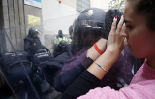 Spanish police push a girl with a shield outside a polling station in Barcelona, on October 1, 2017