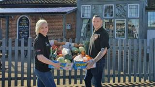 Trina Lake and Bradley Richards with boxes of fruit and vegetables