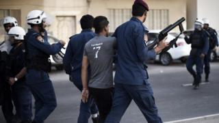 Bahrain riot policemen arrest a protester during clashes on 23 May 2015 in a village west of Manama