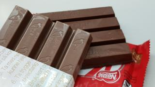 Two similar-looking chocolate bars are arrayed on a table - one embossed with a stork, the other with the Kit Kat logo