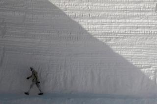 A man walks past a high wall that has been chiselled away.