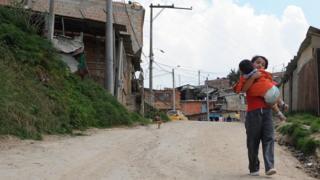 Un niño carga en brazos a otro niño en un barrio de Bogotá.