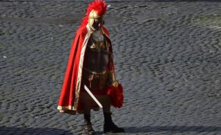 A man dressed as a Roman Centurion waits for tourists near the Ancient Forum on 19 November, 2015 in Rome