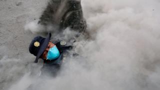 A police officer wearing a blue breathing mask stumbles while running away from a new pyroclastic flow spewed by the Fuego volcano in the community of San Miguel Los Lotes in Escuintla, Guatemala (June 4, 2018)
