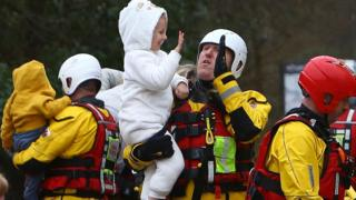 High five: Emergency service workers were praised after hundreds of people were rescued on Sunday