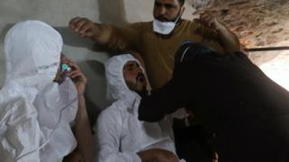 A man breathes through an oxygen mask as another one receives treatment after what rescue workers described as a suspected chemical attack in the town of Khan Sheikhoun in rebel-held Idlib province, Syria (4 April 2017)