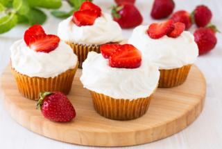 A picture showing strawberry cupcakes with a whipped cream topping