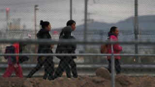 Migrants walk along the US-Mexican border in El Paso, Texas, 10 February