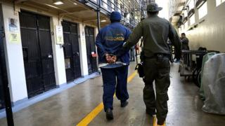 An armed California Department of Corrections and Rehabilitation (CDCR) officer escorts a condemned inamte at San Quentin State Prison's death row on August 15, 2016 in San Quentin, California