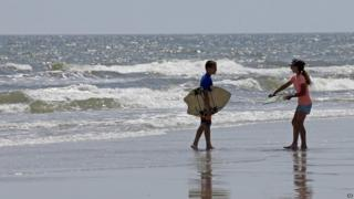 Two children walk with their skim boards on the beach in Oak Island, North Carolina - 15 June 2015