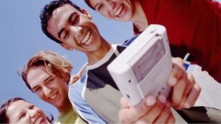 Teens playing on a Gameboy