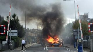 A Vauxhall car on fire near a level crossing in London