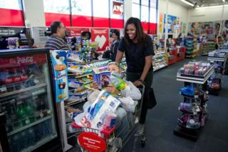 Michelle Obama wheels a loaded trolley - also containing Ellen de Generes - through a pharmacy. Ms De Generes is reading a romance novel while sitting under a selection of groceries.
