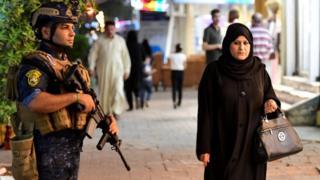 سيدة عراقية تسير في منطقة الكرادة ببغداد