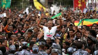 Protestors gesture in front of federal police officers during a protest following the burial ceremony of Simegnew Bekele, Ethiopia's Grand Renaissance Dam project manager