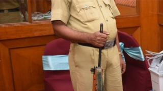 A police constable stands guard beside Voter-Verified Paper Audit Trail (VVPAT) machine during a demo session by the Election Commission of India to the media at a city hotel, on March 26, 2018 in Bengaluru, Indi