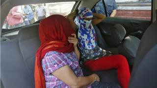 """Two veiled Nepali women, who told police they were raped by a Saudi official, sit in a vehicle outside Nepal""""s embassy in New Delhi, India, September 9, 2015."""