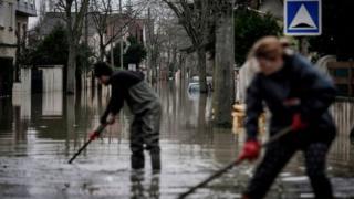 Жители расчищают от мусора улицу, превратившуюся в реку