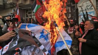 Manifestantes palestinos queman la bandera de Israel.