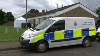 Police van in front of a row of houses with a forensic tent in a garden in the background