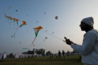 An Indian kite-flying enthusiast flies a hundred kites on a single string during the Delhi International Kite Festival at Golden Jubilee Park in New Delhi on January 24, 2014.