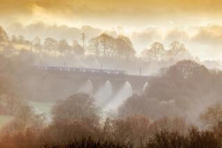 in_pictures Mist is seen in countryside scene as a train crosses a viaduct