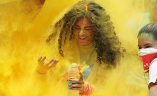 A young woman covered in yellow powder - Saturday 13 April 2019