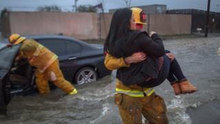 Un bombero evacúa a una mujer de su automóvil, que quedó atrapado en una inundación.