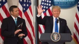 US President Donald Trump waves after speaking alongside Kansas Secretary of State Kris Kobach (L) during the first meeting of the Presidential Advisory Commission on Election Integrity in the Eisenhower Executive Office Building