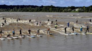People surf and paddle down the Dordogne river during a tidal bore in Saint-Pardon on 24 July 2017.