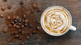 A cappuccino with a caramel web motif pictured next to a pile of coffee beans and grounds.