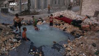 Un cráter sirve de estanque para los niños en Alepo