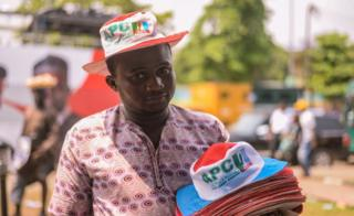 Man selling APC hats