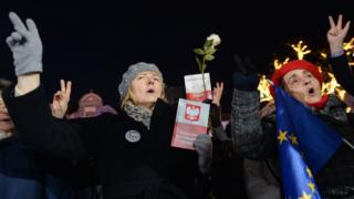 Polish protesters against a controversial new judicial reform law hold copies of the constitution and EU flags in Warsaw