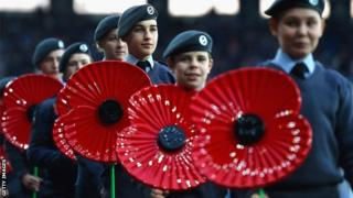 Military personnel carry giant poppies pitchside to mark Remembrance Day