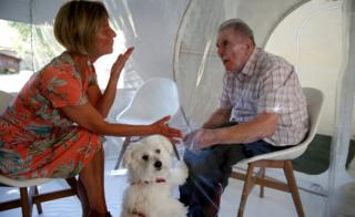 A woman with a dog visits her husband inside a tent, separated by a plastic sheet