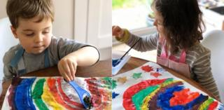 Two children paint rainbows