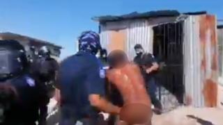 Police officers prevent a naked man from re-entering the house they've forced him out of