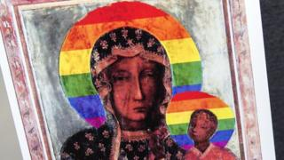 An old-fashioned painting of the Virgin Mary and child is seen printed on a piece of paper - but it has been modified so that the circular halo around both their heads, common to the Byzantine style, has been replaced with a rainbow