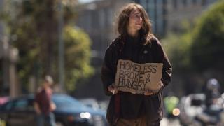 Una mujer sin hogar pide dinero en la calle en San Francisco.