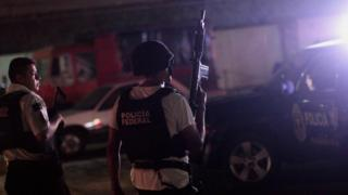 Man in helmet and bulletproof holds machine gun in air; it's night time; the black vest contrasts with his white short sleeved T shirt