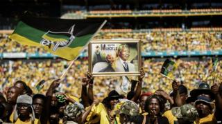 Supporters of South Africa's ruling African National Congress sing and dance while holding a framed poster of late anti-apartheid leader Nelson Mandela during the final ANC election campaign rally at Soccer City stadium in Johannesburg on May 4, 2014.