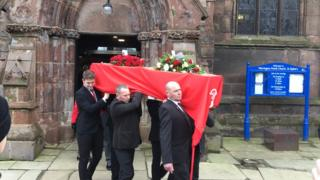 Coffin draped in red LFC banner
