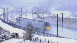 A Eurostar train passes through Ashford, Kent, following heavy overnight snowfall