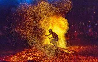 A man performs a stunt by walking barefoot around the burning charcoal to celebrate the Double Ninth Festival at Pan'an County in Jinhua, Zhejiang Province of China