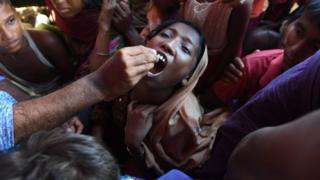 A Rohingya refugee receives an oral cholera vaccine from a Bangladeshi volunteer at the Thankhali refugee camp in Ukhia district (10 October 2017)
