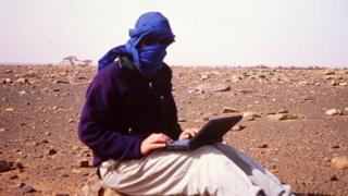 Jeff Greenwald em um terreno aberto e pedregoso, com rosto coberto por pano e laptop no colo