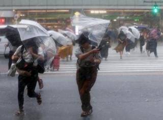 Umbrellas turns inside out as pedestrians struggle across a road in Tokyo