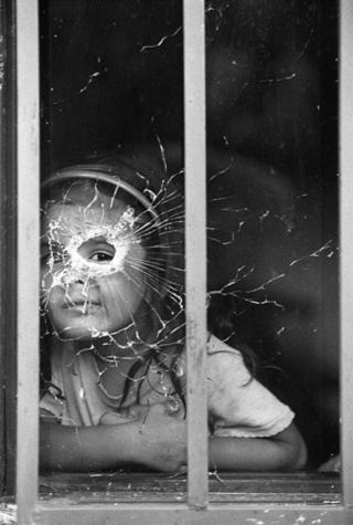 Bir kız çocuğu camda açılmış kurşun deliğinden bakarken