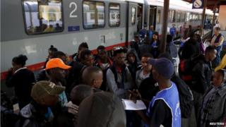 A volunteer talks to a group of migrants as police officers stand in front of the door of a train bound for Munich, Germany, at Bolzano railway station